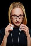Mujer joven con los vidrios y los auriculares Imagenes de archivo