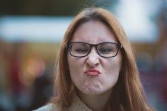 Mujer joven con los vidrios y los labios rojos que hacen las caras, al aire libre Fotografía de archivo libre de regalías