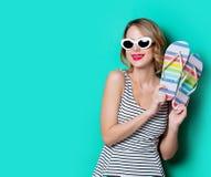 Mujer joven con los zapatos de las chancletas Imagen de archivo
