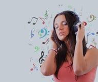 Mujer joven con música que escucha de los auriculares Fotografía de archivo libre de regalías