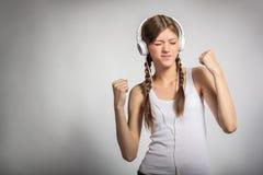 Mujer joven con música que escucha de los auriculares Fotos de archivo libres de regalías
