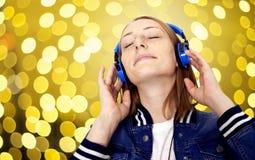 Mujer joven con música que escucha de los auriculares Imágenes de archivo libres de regalías