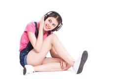 Mujer joven con música que escucha de los auriculares Imagen de archivo