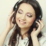 Mujer joven con música que escucha de los auriculares Imagen de archivo libre de regalías