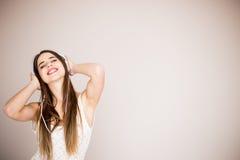 Mujer joven con música que escucha de los auriculares Baile de la muchacha del adolescente de la música contra aislado Imagen de archivo libre de regalías