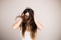 Mujer joven con música que escucha de los auriculares Baile de la muchacha del adolescente de la música contra aislado Foto de archivo