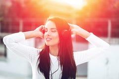 Mujer joven con música que escucha de los auriculares en puesta del sol Fotografía de archivo libre de regalías