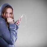 Mujer joven con música que escucha del teléfono elegante Fotos de archivo
