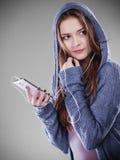 Mujer joven con música que escucha del teléfono elegante Fotos de archivo libres de regalías