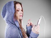 Mujer joven con música que escucha del teléfono elegante Foto de archivo libre de regalías