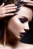 Mujer joven con maquillaje creativo y labios violetas con una pendiente y chispas en la cara Modelo hermoso con los clavos brilla Fotografía de archivo libre de regalías