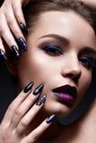 Mujer joven con maquillaje creativo y labios violetas con una pendiente y chispas en la cara Modelo hermoso con los clavos brilla Fotos de archivo libres de regalías