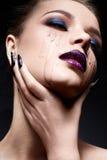 Mujer joven con maquillaje creativo y labios violetas con una pendiente y chispas en la cara Modelo hermoso con los clavos brilla Imagen de archivo