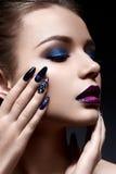 Mujer joven con maquillaje creativo y labios violetas con una pendiente y chispas en la cara Modelo hermoso con los clavos brilla Fotografía de archivo