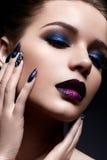 Mujer joven con maquillaje creativo y labios violetas con una pendiente y chispas en la cara Modelo hermoso con los clavos brilla Imagen de archivo libre de regalías