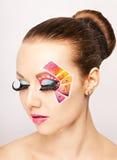 Mujer joven con maquillaje de la moda usando las pestañas falsas Imagen de archivo