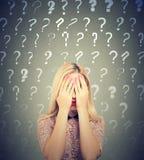 Mujer joven con muchas preguntas y ninguna respuesta que la cubren ojos con las manos que evitan problema foto de archivo