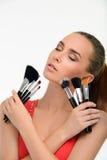 Mujer joven con muchos cepillos del maquillaje Imagenes de archivo