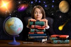 Mujer joven con muchos libros en el escritorio fotografía de archivo