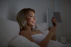 Mujer joven con PC de la tableta en dormitorio de la cama en casa Imagen de archivo libre de regalías