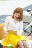 Mujer joven con PC de la tableta en el parque Imagen de archivo libre de regalías
