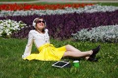 Mujer joven con PC de la tableta en el parque Fotografía de archivo