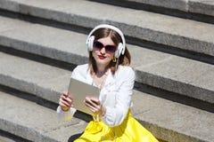 Mujer joven con PC de la tableta en el parque Imagen de archivo