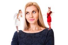 Mujer joven con pequeño ángel y demonio en sus hombros Imagen de archivo libre de regalías