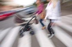 Mujer joven con pequeños niños y un cochecito de niño que camina abajo del stre Fotografía de archivo libre de regalías