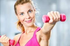 Mujer joven con pesas de gimnasia Imagenes de archivo
