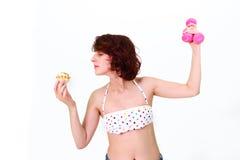 Mujer joven con pesas de gimnasia y la torta Imagen de archivo