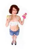 Mujer joven con pesas de gimnasia y la torta Fotos de archivo libres de regalías
