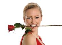 Mujer joven con Rose en boca Foto de archivo