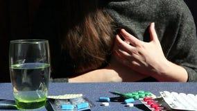 Mujer joven con síntomas del ataque del corazón y medicina, drogas en la tabla almacen de video