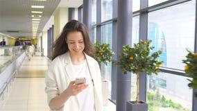 Mujer joven con smartphone en aeropuerto internacional Pasajero de la línea aérea en un avión del vuelo del salón del aeropuerto  almacen de metraje de vídeo