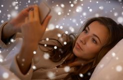 Mujer joven con smartphone en dormitorio de la cama en casa Imagenes de archivo