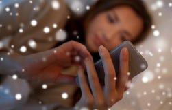 Mujer joven con smartphone en dormitorio de la cama en casa Imagen de archivo libre de regalías