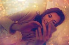 Mujer joven con smartphone en dormitorio de la cama en casa Fotografía de archivo libre de regalías