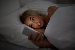 Mujer joven con smartphone en dormitorio de la cama en casa Fotos de archivo libres de regalías