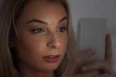 Mujer joven con smartphone en la noche Fotografía de archivo libre de regalías