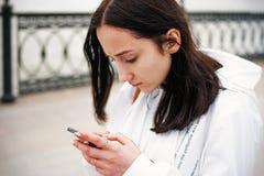Mujer joven con smartphone en mandar un SMS de las manos Imagen de archivo