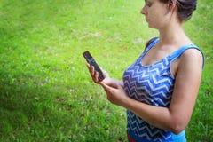 Mujer joven con smartphone moderno en fondo verde del parque Fotos de archivo libres de regalías