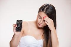 Mujer joven con smartphone quebrado Foto de archivo libre de regalías
