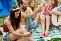 Mujer joven con smartphone y amigos en acampar Imágenes de archivo libres de regalías