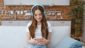 Mujer joven con smartphone y los auriculares en casa