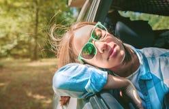 Mujer joven con su cabeza sobre el coche de la puerta Fotografía de archivo libre de regalías