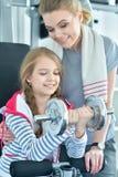 Mujer joven con su hija adolescente en un gimnasio con pesas de gimnasia Imagenes de archivo