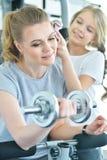 Mujer joven con su hija adolescente en un gimnasio con pesas de gimnasia Imagen de archivo libre de regalías