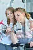 Mujer joven con su hija adolescente en un gimnasio con pesas de gimnasia Fotografía de archivo libre de regalías