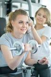 Mujer joven con su hija adolescente en un gimnasio con pesas de gimnasia Foto de archivo